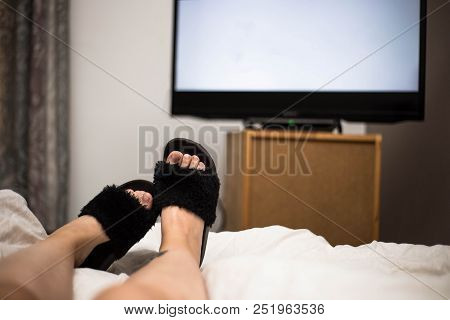 Person Watches Tv At Night In His Bed With His Feet Wearing Black Flip Flops. The Tv Screen Is Blank