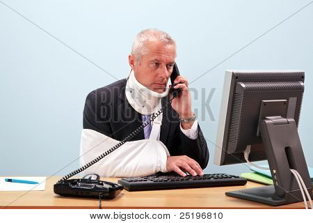 Photo of a mature businessman with injuries talking on the phone whilst trying to work on his computer. Good image for health and safety or accident at work related themes.