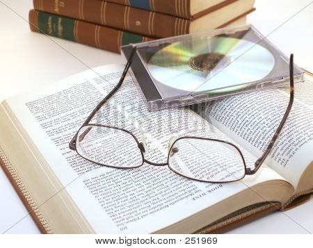 Glasses And Cd On Open Book