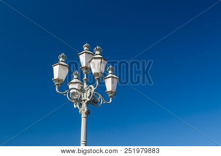 Decorative Lamppost With Multiple Lanterns In Broad Day Light.
