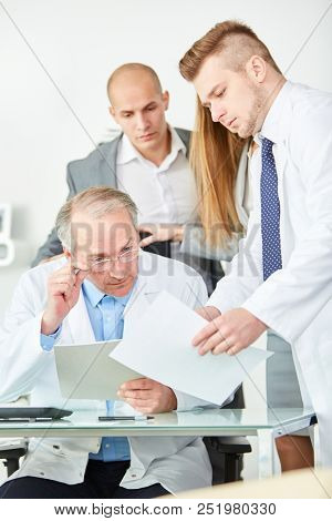 Senior physician as clinic chief executive with team of doctors
