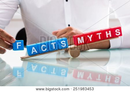 Businessman's hand showing unbalance between facts and myths on wooden seesaw poster