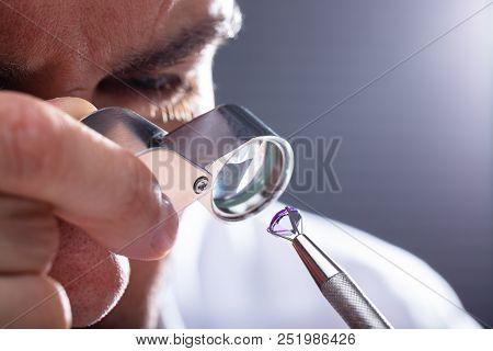Jeweler Looking At Diamond Through Magnifying Loupe