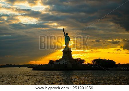 Statue Of Liberty At Ellis Island In New York City At Sunset