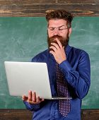 Distance education concept. Surfing internet. Hipster teacher wear eyeglasses and necktie holds laptop surfing internet. Teacher bearded man with modern laptop surfing internet chalkboard background. poster