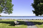 Bench in the park at Canandaigua Lake. View of the calm blue lake, sidewalk to the lakeshore in the summer. New York Finger Lakes, poster