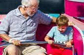 An elderly man and his young grandson ride a carnival ride at a theme park.  The white haired man looks at the boy with a smile as the child hangs on tight to the safety bar and leans to whirl faster. poster