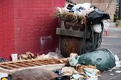 overfilled trash dumpster in ghetto neigborhood against red wall poster