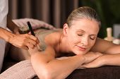 Relaxed mature woman enjoying a mud skin treatment at spa. Portrait of beautiful senior woman having clay body mask applyed by beautician in a wellness center. Exfoliation scrub beauty treatment. poster