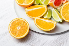 Pieces Of Citrus Fruits On White Plate