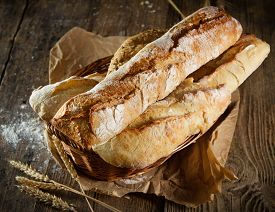 Heap Of Fresh Baked Bread On Wood Background