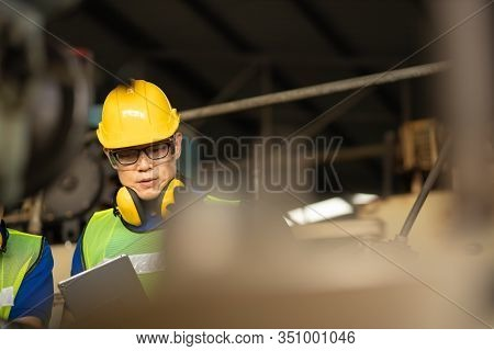Engineer Looking Of Working At Industrial Machinery Setup In Factory.men Industrial Engineer Wearing