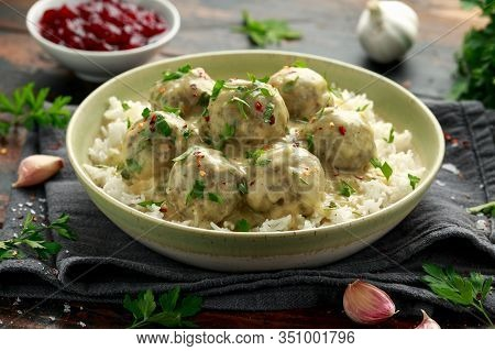 Hot Swedish Meatballs With White Rice And Cranberry Sauce On Wooden Table