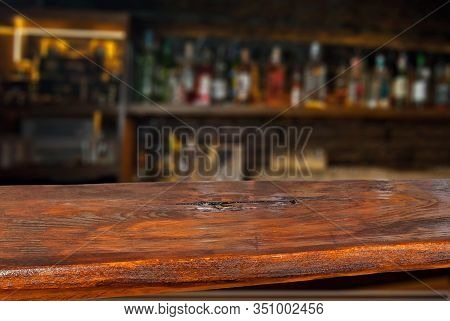 Wooden Board On A Background Of Bottles With Alcohol. Old Bar Counter As Layout For Design. Workpiec