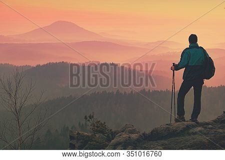 Man Walk To Camp By Trekking Rocky Route. Backpacker Carrying Backpacks And Using Trekking Poles And