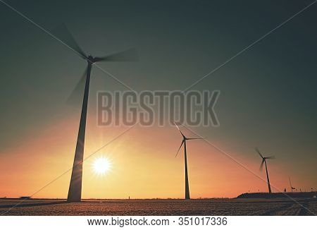 Wind Power Mills In Colorful Freeze Fog On Hoarfrost Meadow, Germany.