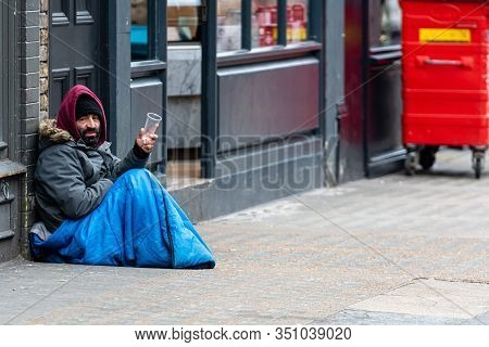 London, England, Uk - January 2, 2020: A Bearded Man Sitting On The Sidewalk And Begging From Passer