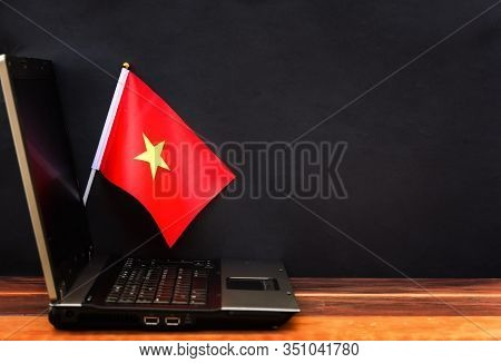 Flag Of Vietnam , Computer, Laptop On Table And Dark Background