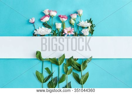 Blank Oblong Sheet Of Paper On Blue Background. Sprigs With Pink And White Flowers, Green Leaves Are
