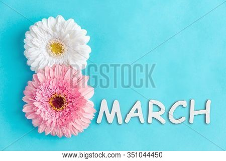 Inscription 8 March Made Of Two Pink And White Gerbera Flowers On Blue Background. Greeting Card Tem