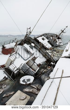 Old fishing ship sank at the pier in the port in winter. Environmental pollution.