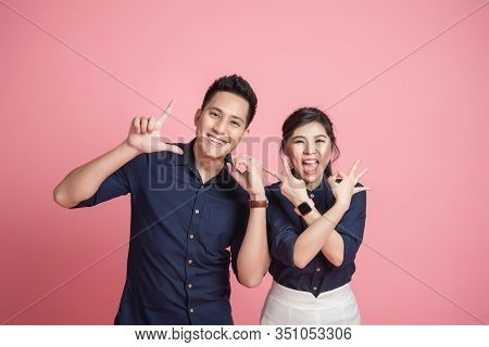 Happy Asian Couple Doing Love Hand Sign Gesture