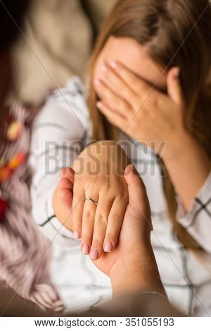 A Mans Hand Holds A Womans Hand. The Girl Has An Engagement Ring With A Diamond. In The Background,