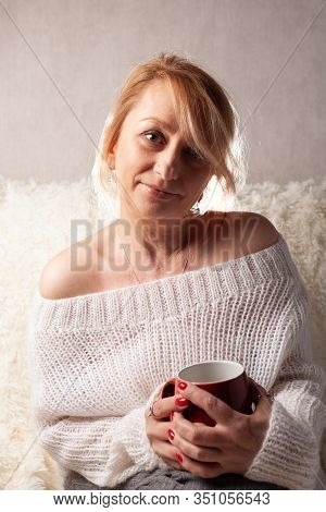 Portrait Of An Adult Woman In A Cozy Room On The Couch With A Cup Of Tea / Coffee.