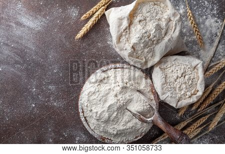 Wooden Bowl Of Wheat Flour On Kitchen Background Top View. Ingredient For Baking.