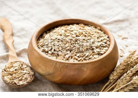 Rolled Oats, Oat Flakes In Wooden Bowl. Healthy Food, Dieting, Breakfast Cereals Concept