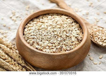 Dry Oat Flakes, Oats, Rolled Oats In A Wooden Bowl. Concept Of Healthy Eating, Dieting, Dietary Fibe
