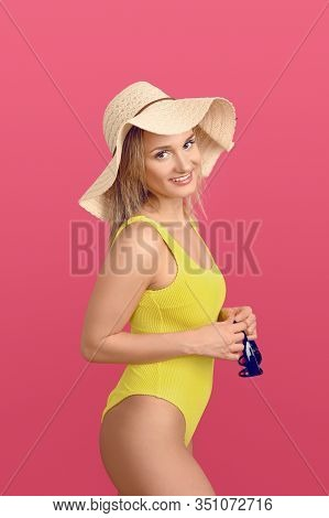 Slender Attractive Young Blond Woman In A Colorful Yellow Swimsuit And Wearing A Wide-brimmed Floppy