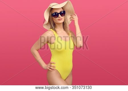 Trendy Sexy Young Blond Woman In A Yellow Swimsuit, Floppy Straw Sunhat And Sunglasses Posing Over A