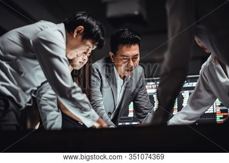Group Of Asian Business Financial Team In Strategic Meeting, Work Late Night Shift In Office. Busine