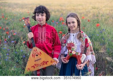 Portrait Of A Boy And A Girl In The Field. On The Girl Is A Shawl With Folk Patterns. In The Hands O