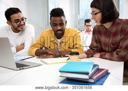 Multy-ethnic group of young business people sitting at the office desk and working with computer. Multy-ethnic group of students study in a computer class together