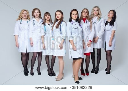 Feminism. Full Length Portrait Of A Successful Group Of Doctors Staying In Front Of Grey Background