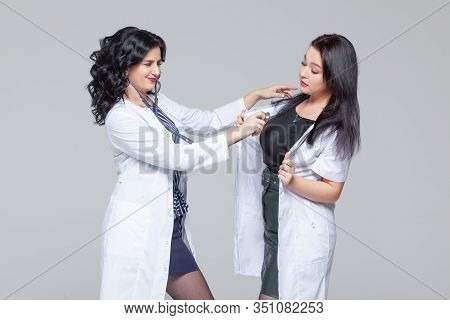 Female Doctor Examining Another Woman With Stethoscope