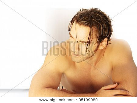 Good-looking man laying on table with bare torso in warm golden toned light with plenty of copy space