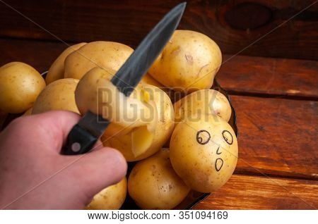 Light Potato Looks At A Sharp Knife. Concept Of Fear Of A Sharp Object. Killing With A Knife