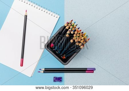 Colored Pencils In A Black Office Cup, Purple Pencil Sharpener, A Pair Of Sharpened Pencils And A No