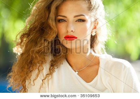 Closeup portrait of a beautiful young brunette woman with natural makeup, perfect skin and gorgeous curly hair outdoors