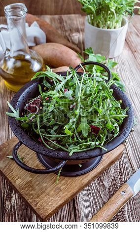 Fresh Organic Arugula Leaves In Black Colander. Arugula Or Rucola For Salad On Wooden Rustic Backgro