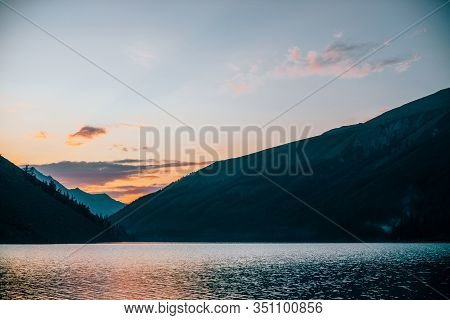 Vivid Dawn Sky Is Reflected In Pure Alpine Lake Near Mountain Silhouettes At Sunrise. Colorful Scene