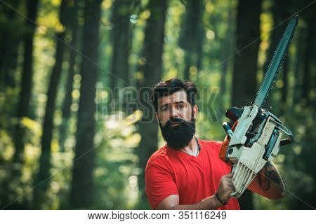 Lumberjack In The Woods With Chainsaw Axe. Professional Lumberjack Holding Chainsaw In The Forest. W