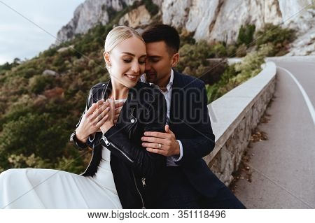 Young Newly Wed Couple, Bride And Groom Kissing, Hugging On Perfect View Of Mountains, Wedding Conce
