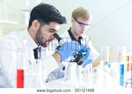 Team Of Scientist Research Working Together Conduct Experiments And Looks On  Microscope In Modern L