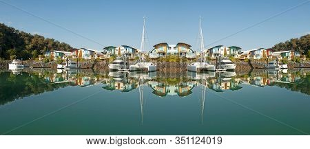 Waterfront Resort Marina/dock With Boats And Clear Tropical Water Reflections With Blue Sky Backdrop