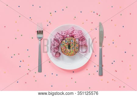 Abstract Funny Face Of Woman Made Donut With Eyes And Hair From Centimeter Tape On Plate, Cutlery On