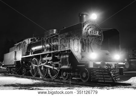 An Old Steam Engine With The Lights On At The Rural Town In Finland. The Lights Shine Beautifully On